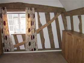 Photo:Diagonal brace upstairs. Note the arched tie beam - a sign of quality construction.