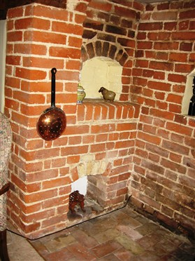Photo:Inglenook bread oven at Orchard Cottage. Note the access below to remove ashes, and the smoke blackened bricks above the opening.