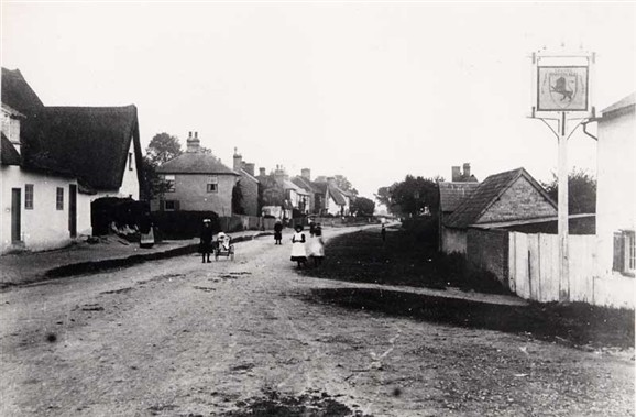 Photo:The Red Lion stood at the eastern end of the thatched wall. Village lockup beyond