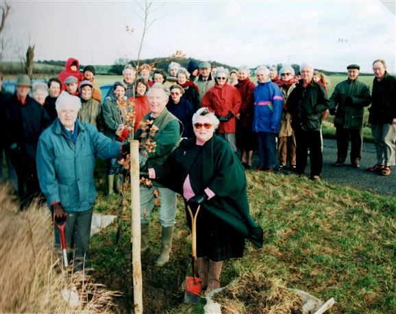 Photo:Villagers watch as Gordon Lines and Joan Stammers plant the final tree