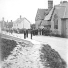 Photo:These cannot be military men! Note that almost every hand is in a pocket. Note also the thatched cottages further up the street.